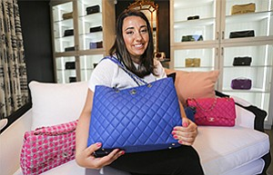 Christina Samoylov, owner of Designer Vault, shows off one of her Chanel purses. The Carlsbad company specializes in gently used and vintage Chanel.