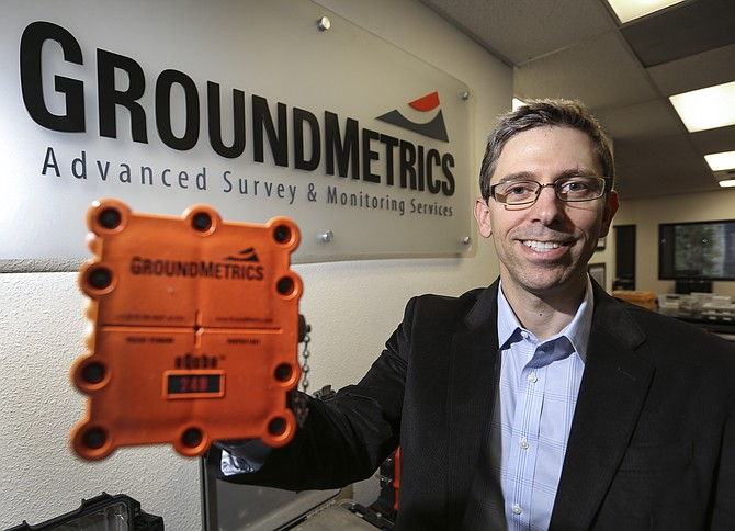 GroundMetrics CEO George Eiskamp holds an eQube, which is used to collect data in the desert.