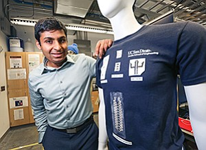 Rajan Kumar, a UC San Diego doctoral student and founder of Ocella, stands with a mannequin in the university's nanobioelectronics lab. The mannequin's T-shirt carries a variety of sensors.