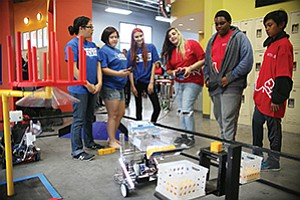 A group of young people conduct a science experiment at the new STEM facility in the Ron Roberts Family Boys & Girls Club made possible by funding from Raytheon Co.  Photo by Sandy Huffaker / AP Images for Boys & Girls Clubs of America