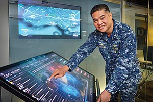 Capt. Melvin Yokoyama Jr. assumed command of Spawar Systems Center Pacific, the U.S. Navy lab on Point Loma, in May. Here he demonstrates technology that the lab calls the command center of the future. Photo courtesy of Spawar Systems Center Pacific
