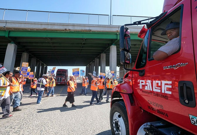 Roadblock: Workers strike at a warehouse in Wilmington in June.