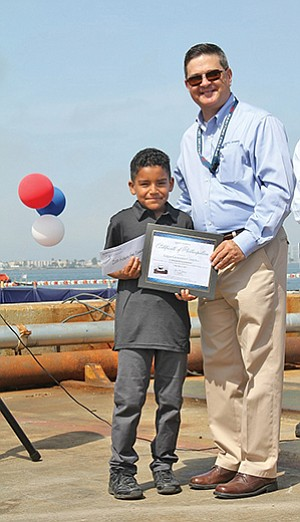 Edgar Cordoba of King Chavez Academy of Excellence in Barrio Logan is presented the award by General Dynamics NASSCO President Kevin Graney, for winning the contest to name the company's newest tugboat. Photo courtesy of General Dynamics NASSCO