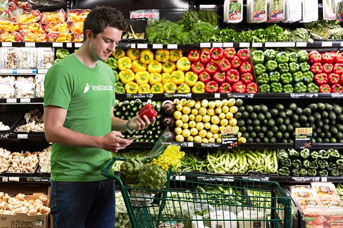 Looking to Produce More: Instacart employees fill out and deliver digital orders.