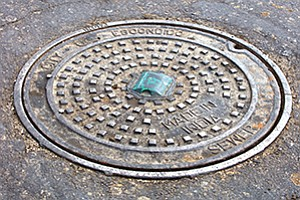 This manhole in Escondido hides electronics from SmartCover Systems inside. The reflector houses an antenna that lets the water-level sensor inside send information to the Iridium satellite network.
