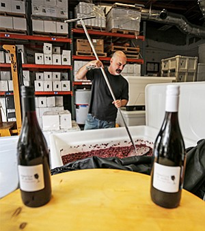 "Eric Van Drunen, who recently opened urban winery Charlie & Echo in Miramar, uses a device to ""punch down"" grape skins in a tank of fermenting red wine. Urban wineries produce wine in industrial and commercial areas rather than at vineyards."