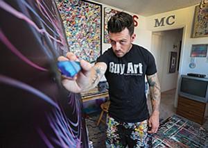 Artist Michael Carini paints in his studio.