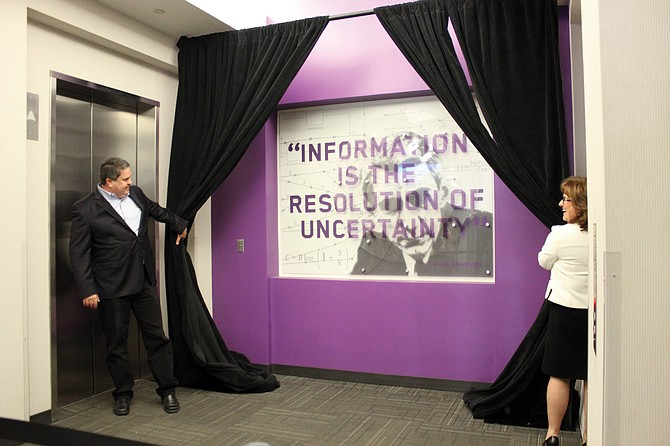 Qualcomm executives Matt Grob and Erica Fessia pull curtains to reveal one of the new art installations at the Qualcomm Research Center in a ceremony on Oct. 26, 2017. Students from San Diego City College designed six installations with the common theme of Great Minds. The artwork here shows engineer Claude Shannon, who is considered the father of modern digital communications. Photo courtesy of Qualcomm Inc.
