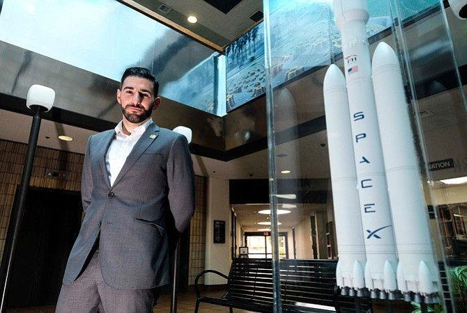 Hawthorne City Councilman Haidar Awad next to SpaceX model rocket.