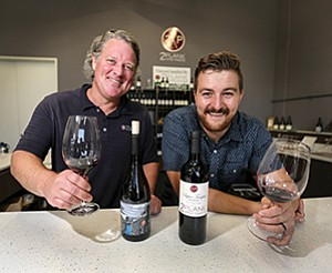 Jason Wimp, an owner of 2Plank Urban Winery, and winemaker Mike Szymczak show off some of the winery's top offerings at its tasting room in Vista. The winery uses grapes from its vineyard in Fallbrook as well as from other vineyards.