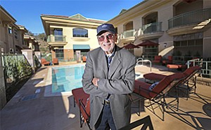 Above, Richard Cavanaugh stands in the center of the 54-unit apartment complex he developed alongside a Rancho Santa Fe retail center which are the final elements of the Whispering Palms project he started 55 years ago.