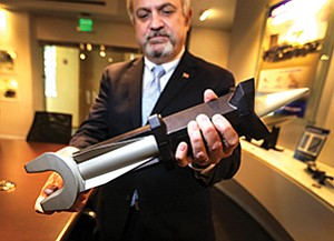 GA-EMS President Scott Forney holds a railgun projectile. The gray, missile-shaped projectile sits within a sabot, a black casing that guides it down the gun barrel and then falls away. The railgun is only part of the business at the lesser-known unit of General Atomics.