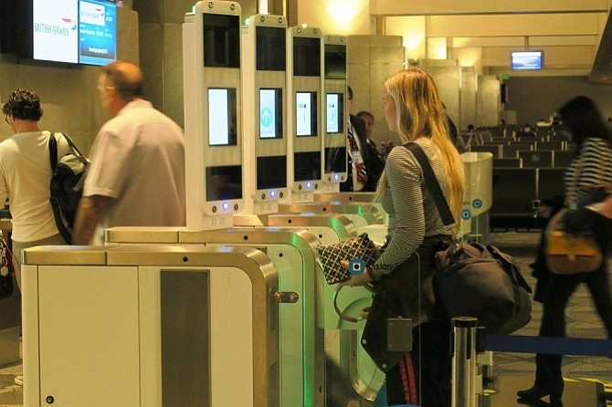 """British Airways passengers boarding a  flight  at Los Angeles International Airport through the biometric """"E-Gate,"""" which uses facial-recognition technology developed by Portuguese company Vision-Box."""