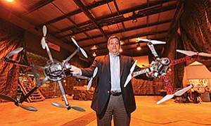 Rod Weiss of Coleman University holds two aircraft at the Hornet's Nest, Coleman University's indoor drone test site, following its grand opening in early 2017.