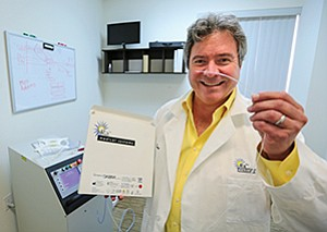 Ra Medical Systems CEO Dean Irwin in a file photo holds the company's Dabra system, a laser catheter to treat a disease known to lead to amputations. He recently expressed relief over the suspension of a medical device tax that threatened hiring plans.