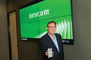 Dexcom CEO Kevin Sayer holds out his smartphone with Dexcom's app. The company's technology continuously monitors diabetes patients' blood glucose levels.