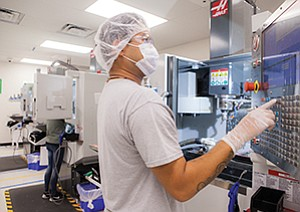 Khris Contemprato, an operator of Dexcom's transmitter manufacturing line in San Diego, presses the start cycle on the computer numerical control mill to give the transmitter its final shape. Dexcom's technology includes a sensor — typically on a patient's abdomen — that measures just below the skin, and a transmitter relays glucose level data every five minutes to a smart device.