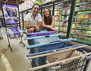 Farzan and Jen Dehmoubed, owners of Lotus Trolley Bag, in an aisle inside the Ralphs at 7140 Avenida Encinas in Carlsbad, displaying reusable grocery bags they created.