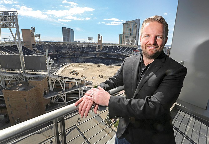 Jeff Winkler, CEO of Origin Code Academy, stands on a balcony at the company's new office in DiamondView East Village, a 15-story office tower next to Petco Park.