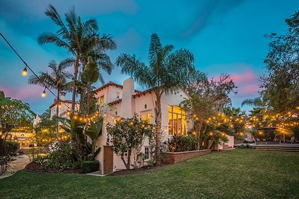 A view of the 0.4-acre lot at dusk that has multiple elevations and entertainment areas. Photo courtesy of Coldwell Banker Residential Realty
