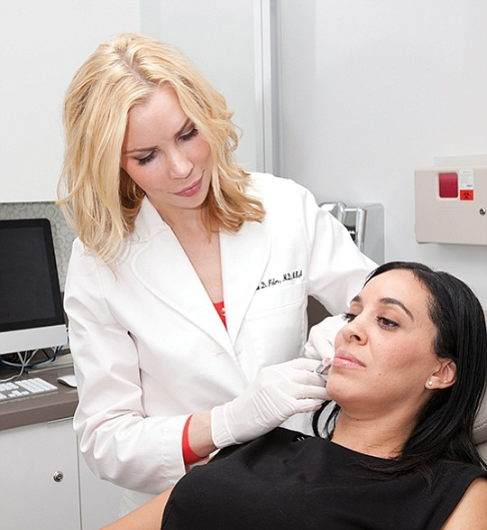 Dr. Melanie Palm injects a hyaluronic acid filler to reestablish facial balance for one of her cosmetic patients at Art of Skin MD in Solana Beach. Hyaluronic acid fillers are used to restore volume loss due to the aging process and typically last between 6-12 months. Photo courtesy of Melanie Palm