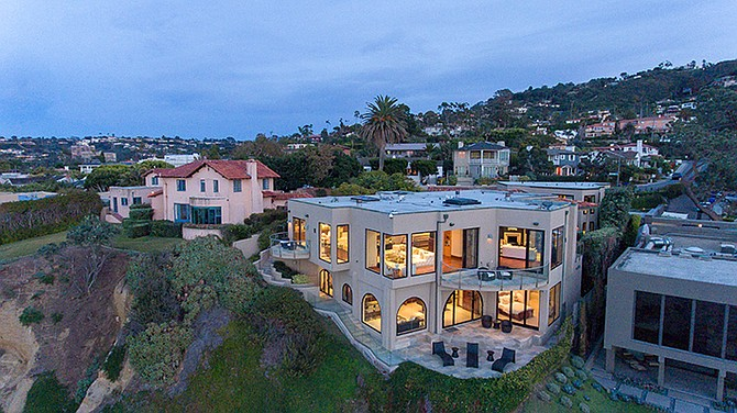 An aerial twilight view of 1828 Spindrift Drive in La Jolla that is perched on the dramatic sandstone palisades above La Jolla Cove. Photo courtesy of Coldwell Banker Residential Brokerage