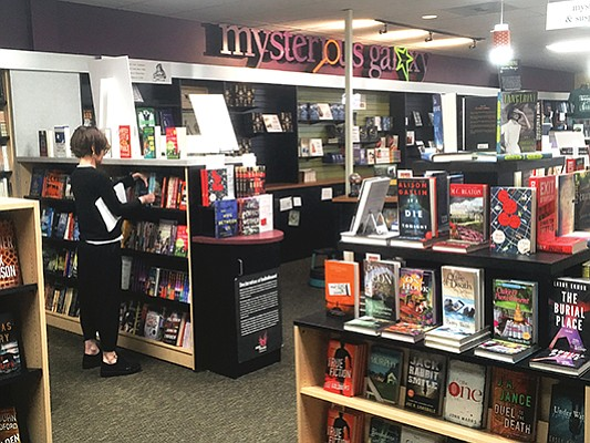 A patron browses the shelves at the independent Mysterious Galaxy Bookstore.