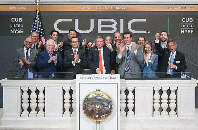 Cubic Corp. CEO Brad Feldmann rings the closing bell on the New York Stock Exchange June 13. At far left is Matt Cole, head of the transportation unit. V.P. John Roberti is at far right. Photo courtesy of Cubic Corp.