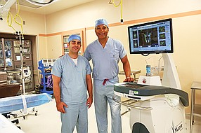 Dr. Payam Moazzaz (left) and Dr. Neville Alleyne in front of Tri-City Medical Center's Mazor robotic system. Tri-City is among the San Diego hospital systems that have embraced robotic surgery. Photo courtesy of Tri-City Medical Center