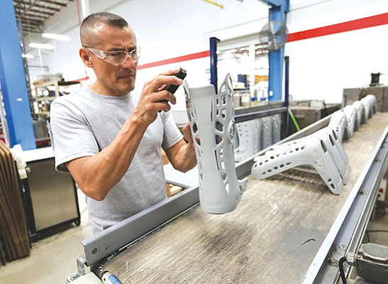 In a file photo, Felipe Sanchez smooths the edges of walking boots at DJO Global's Tijuana manufacturing facility. DJO Global, based in Vista, specializes in orthopedic products.