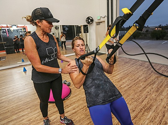 Lisa Druxman, chief founding mom at Fit4mom, left, trains Desiree Vorhees and others at an early morning fitness class in San Marcos.