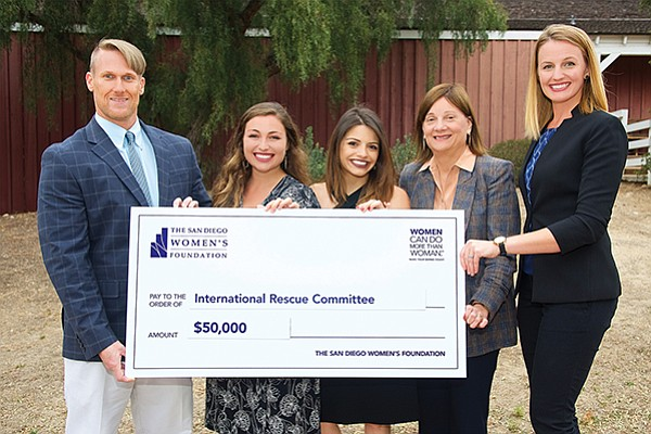 Mitch Johnson, left, with colleagues Allison Ware and Sofia Cortes of the International Rescue Committee accept a $50,000 grant check from The San Diego Women's Foundation representatives, Greta Treadgold and Katie Sawyer. Photo courtesy of The San Diego Women's Foundation