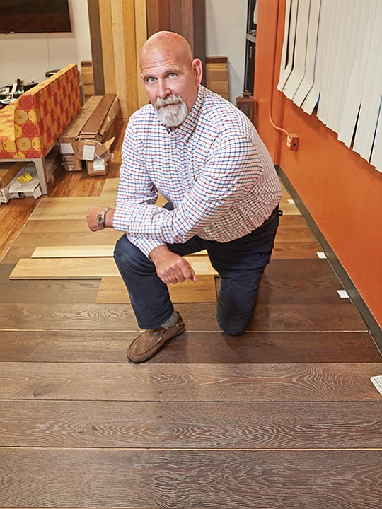 Cali Bamboo's new CEO, Doug Jackson, kneels on flooring samples in the company's R&D studio.