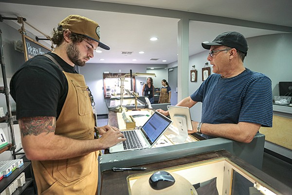 OutCo Assistant Manager Rhettry Griebel, left, uses a cannabis-specific retail operations platform developed by Yobi, a local software startup, to track sales at the dispensary in El Cajon.