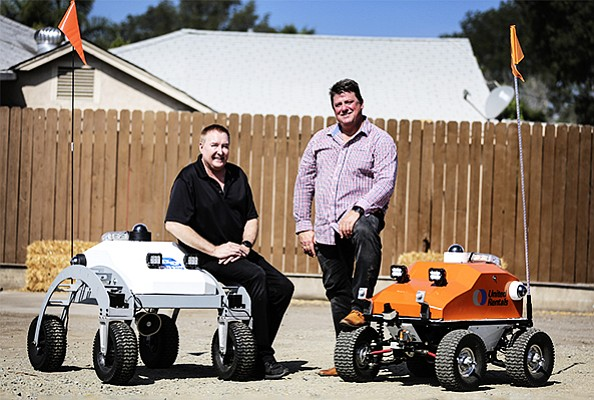 From left to right, Nxt Robotics Chief Technology Officer Tom Caldwell and CEO Darin Andersen with two iterations of the company's autonomous security robot at Nxt's testing ground in El Cajon. The orange vehicle is the latest version.