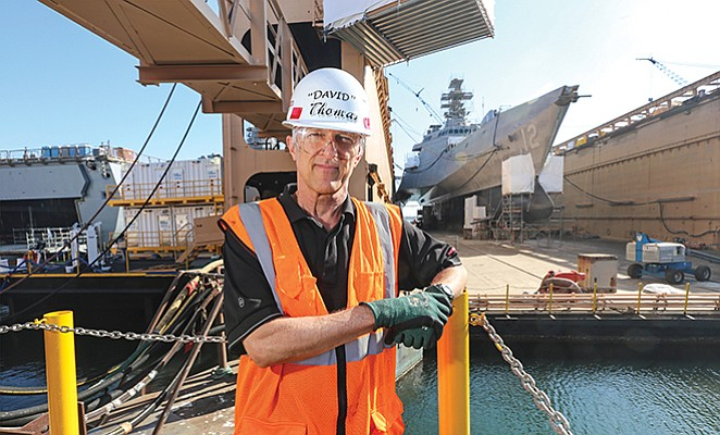 Retired Rear Adm. David M. Thomas manages the BAE Systems San Diego Ship Repair yard. The walkway at upper left gives shipyard employees access to the dry dock holding the USS Omaha.