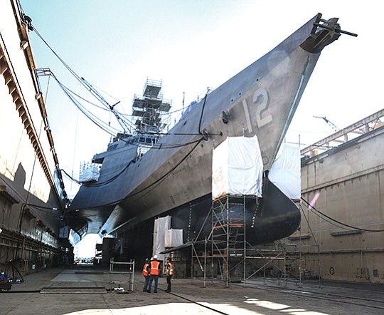 Workers at BAE Systems San Diego Ship Repair confer beneath the USS Omaha in dry dock. The 104-foot-wide littoral combat ship barely fits within the dry dock.