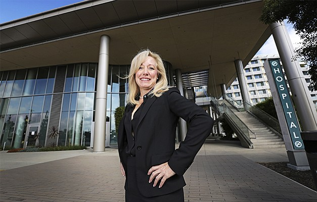 Diane Hansen stands in front of Palomar Medical Center Escondido. A whirlwind of accomplishments as interim CEO led to the role becoming permanent.