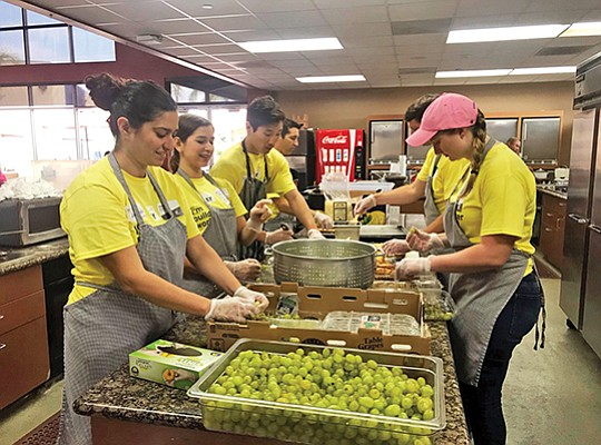 Ernst & Young LLP volunteers help prepare meals for families in San Diego at Ronald McDonald House as part of the company's EY Connect Day, one of nine volunteer projects. Photo courtesy of Basir Mohammad