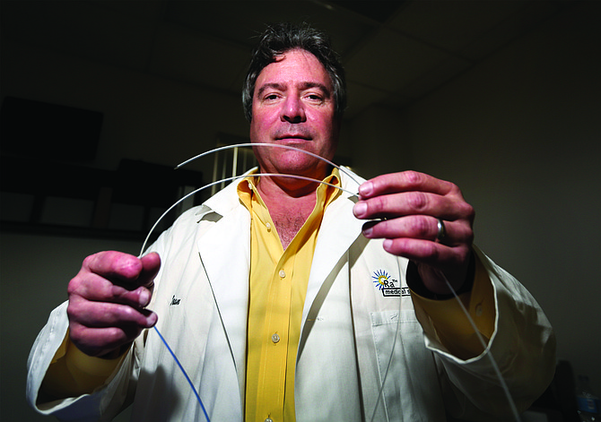 Ra Medical Systems CEO Dean Irwin in a file photo holds the company's Dabra system, a laser catheter to treat a disease known to lead to amputations. He recently expressed relief over the suspension of a medical device tax that threatened hiring plans. File photo by Jamie Scott Lytle