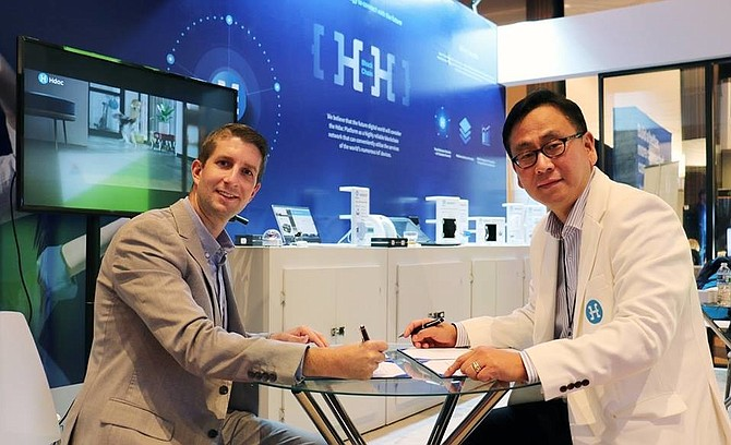 Conectric CEO Phillip Kopp and Hdac Chief Operating Officer John Sang-Ug Bae sign an agreement to co-develop an IoT blockchain solution.