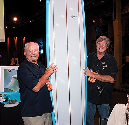 Joe Tudor, left, and Craig Hollingsworth hold a surfboard that was auctioned off at the third annual benefit concert for Scripps Memorial Hospital Encinitas. Photo courtesy of Scripps Memorial Hospital