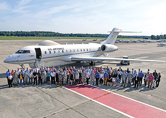Employees at Hanscom Air Force Base in Massachusetts pose with an E-11A aircraft, a conventional passenger plane from Bombardier that carries BACN electronics above a battlefield. The Air Force manages the BACN program at the Massachusetts base. Photo by Mark Herlihy courtesy of U.S. Air Force