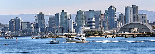 A view of San Diego Bay reflects the region's diverse economy: hotels and other high-rise buildings downtown with military buildings — and helicopters — at right at Naval Air Station North Island.