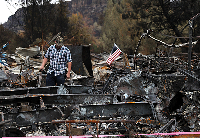 Remaining Ruins: Paradise resident Noah Fisher looks through the rubble where his home once stood after the Camp Fire swept through the tiny town in Butte County.