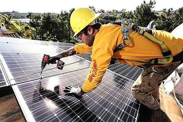 Sullivan Solar Power employee Jonathan Rogers installs solar panels atop a home in Carlsbad. California will require solar panels on all new homes starting in 2020. The mandate was approved by the California Energy Commission in 2018 as part of an update to the panel's energy efficiency standards, which are revisited every three years.