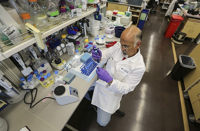 Andres Berdeja, a research assistant with Ionis Pharmaceuticals, works in the Carlsbad company's lab. Ionis said it wasn't impacted by the 35-day government shutdown. But another shutdown could embroil more biotechs.