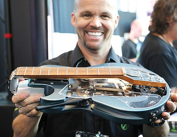 Jonathan Spangler designed full-sized, portable guitars that can be carried on an airplane. A switch lowers the tension in the guitar's strings, allowing it to fold at the neck. Photo courtesy of Ciari Guitars