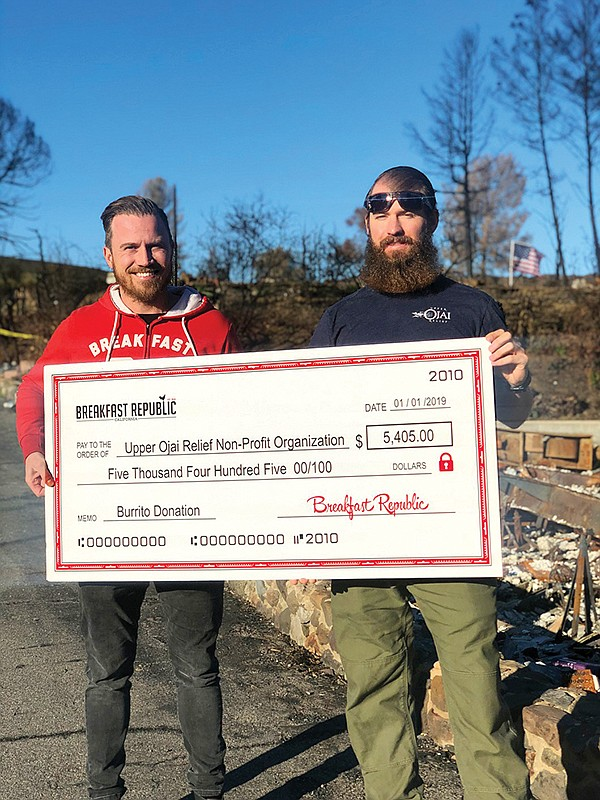 Johan Engman, owner/founder of Rise & Shine Restaurant Group, left, presents a check to Justin Homze, board member for Upper Ojai Relief. Photo courtesy of Rise & Shine Restaurant Group