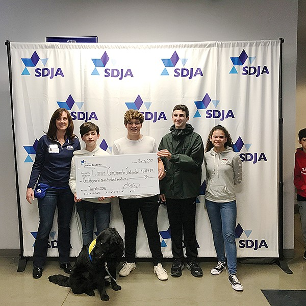 Joanna Mueller, development director at Canine Companions for Independence, left, with San Diego Jewish Academy students Martin Kohan, Alexander Russo, Mathew Saacks, and Hannah Velasquez at a check presentation. Photo courtesy of San Diego Jewish Academy